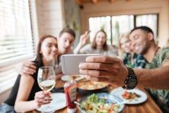 Groupe d'amis mangeant et prenant le selfie à la table Photographie stock