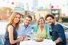 Groupe d'amis mangeant le repas sur la terrasse de dessus de toit Photos stock