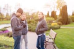 Groupe d'amis marchant au printemps parc Fond brouillé Photographie stock libre de droits