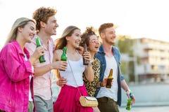 Groupe d'amis marchant avec des bières dans leurs mains Images stock