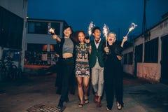 Groupe d'amis marchant avec des cierges magiques sur la route dans la soirée Photographie stock