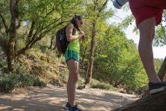 Groupe d'amis marchant avec des sacs à dos dans le sac à dos de forêt augmentant dans les bois Risquez, voyagez, tourisme, repos  Images libres de droits