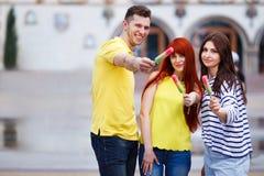Groupe d'amis marchant dans la ville mangeant la crème glacée, plaisantant, h Photo stock