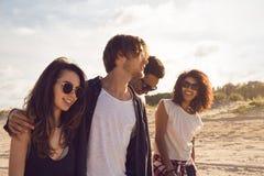 Groupe d'amis marchant ensemble sur la plage Photos libres de droits
