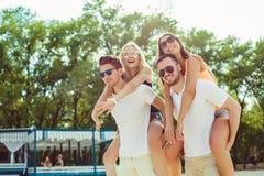 Groupe d'amis marchant le long de la plage, avec les hommes donnant sur le dos le tour aux amies Image stock