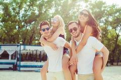 Groupe d'amis marchant le long de la plage, avec les hommes donnant sur le dos le tour aux amies Photos libres de droits