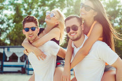Groupe d'amis marchant le long de la plage, avec les hommes donnant sur le dos le tour aux amies Image libre de droits