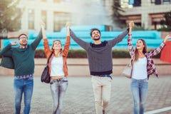 Groupe d'amis marchant le long de la rue avec des paniers Photographie stock