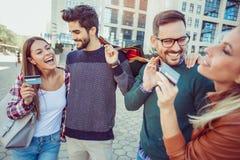Groupe d'amis marchant le long de la rue avec des paniers Photographie stock libre de droits