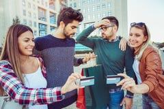 Groupe d'amis marchant le long de la rue avec des paniers Photo stock