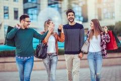 Groupe d'amis marchant le long de la rue avec des paniers Images stock