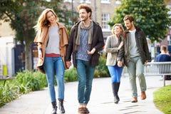 Groupe d'amis marchant par le parc de ville ensemble Images stock