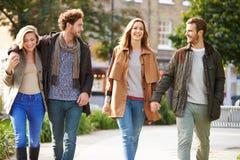 Groupe d'amis marchant par le parc de ville ensemble Photographie stock
