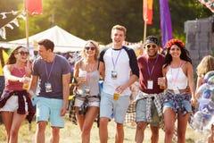 Groupe d'amis marchant par un site de festival de musique Image libre de droits