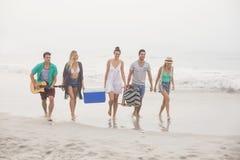 Groupe d'amis marchant sur la plage Images stock