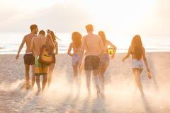 Groupe d'amis marchant sur la plage au coucher du soleil Photos stock
