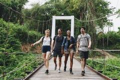 Groupe d'amis marchant sur le pont dans un concept tropical d'aventure et de voyage de campagne Photo libre de droits