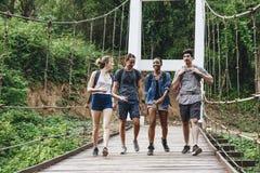 Groupe d'amis marchant sur le pont dans un concept tropical d'aventure et de voyage de campagne Image libre de droits