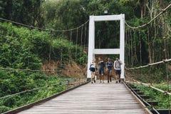 Groupe d'amis marchant sur le pont dans une campagne tropicale Photo libre de droits