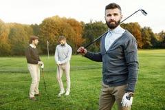 Groupe d'amis marchant sur le terrain de golf Photographie stock libre de droits