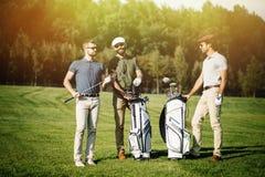 Groupe d'amis marchant sur le terrain de golf Image stock