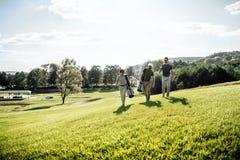 Groupe d'amis marchant sur le terrain de golf Photo libre de droits