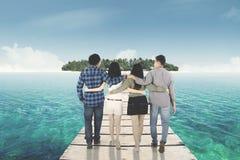 Groupe d'amis marchant vers l'île Image stock