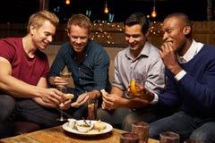 Groupe d'amis masculins appréciant la nuit à la barre de dessus de toit Images stock