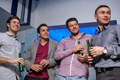 Groupe d'amis masculins avec de la bière dans la boîte de nuit Photo stock