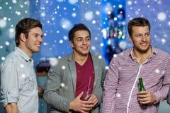 Groupe d'amis masculins avec de la bière dans la boîte de nuit Photos stock