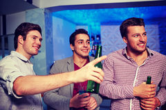 Groupe d'amis masculins avec de la bière dans la boîte de nuit Image stock