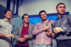 Groupe d'amis masculins avec de la bière dans la boîte de nuit Images libres de droits