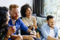 Groupe d'amis masculins et féminins ayant l'amusement à la maison Image stock