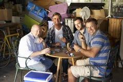 Groupe d'amis masculins jouant des cartes dans le garage Photos stock