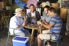 Groupe d'amis masculins jouant des cartes dans le garage Image libre de droits
