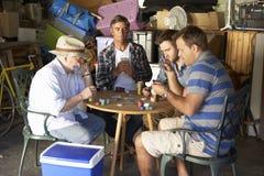 Groupe d'amis masculins jouant des cartes dans le garage Photos libres de droits
