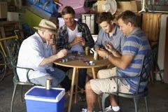 Groupe d'amis masculins jouant des cartes dans le garage Photo stock