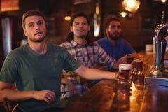 Groupe d'amis masculins observant le match de football Images libres de droits