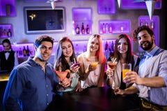 Groupe d'amis montrant le cocktail au compteur de barre Photos stock