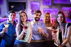 Groupe d'amis montrant le cocktail au compteur de barre Image libre de droits