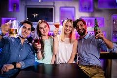Groupe d'amis montrant le cocktail, la bouteille à bière et le verre de bière au compteur de barre Photo stock