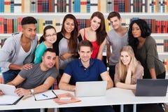 Groupe d'amis multi-ethniques dans la bibliothèque Images stock