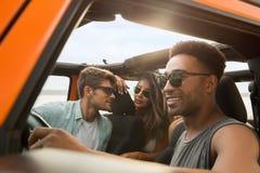 Groupe d'amis multi-ethniques s'asseyant dans une voiture Photos libres de droits