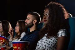 Groupe d'amis multiculturels au théâtre de film Photos stock