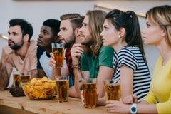 groupe d'amis multiculturels buvant de la bière et regardant le match de football images libres de droits