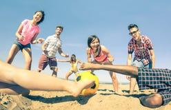 Groupe d'amis multiraciaux jouant le football de plage à l'été Image stock