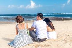 Groupe d'amis multiraciaux s'asseyant sur la plage de l'île tropicale de Bali, Indonésie Photographie stock libre de droits