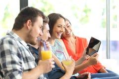 Groupe d'amis observant des vidéos dans un comprimé Photos libres de droits