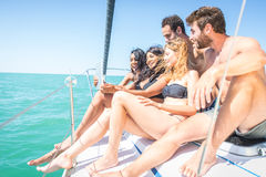 Groupe d'amis observant le comprimé sur un bateau Image stock