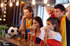Groupe d'amis observant le football dans le bar Photos stock